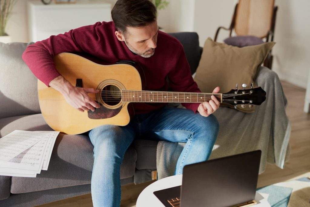 man learning guitar online at home