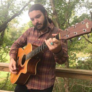 derek kretzer playing guitar outside in nature