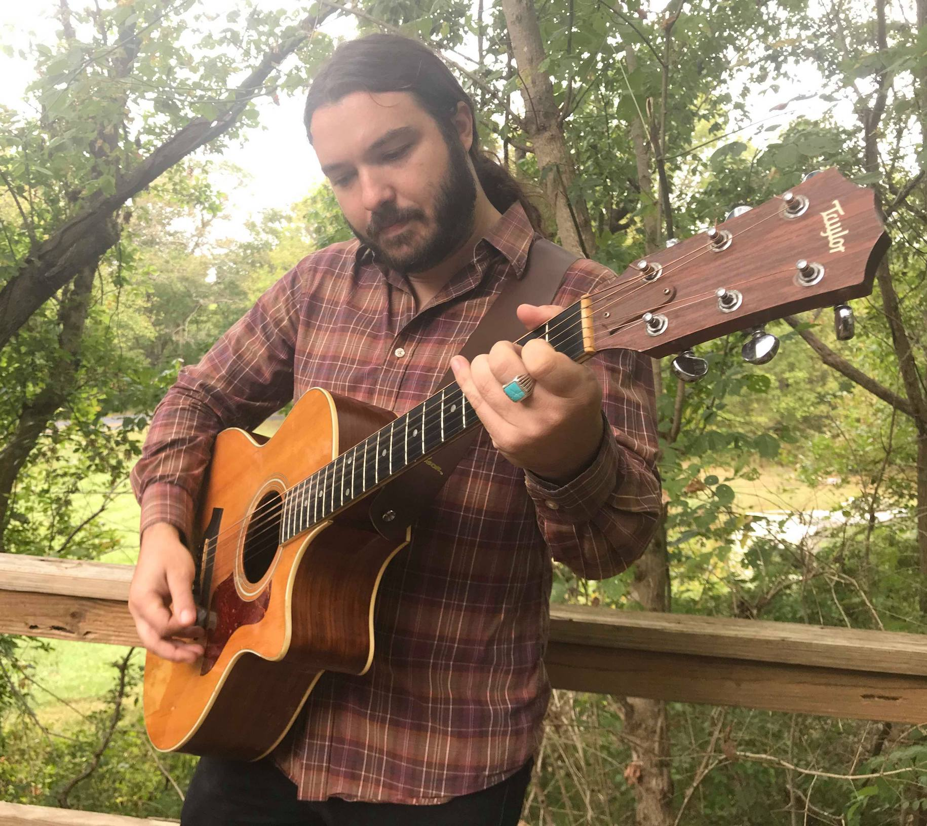 derek kretzer playing guitar outside in nature