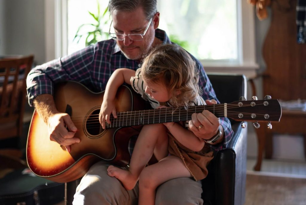 adult teaching a child how to play guitar