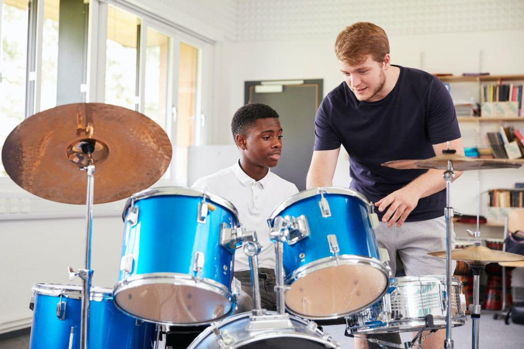 drum instructor teaching student how to play drums