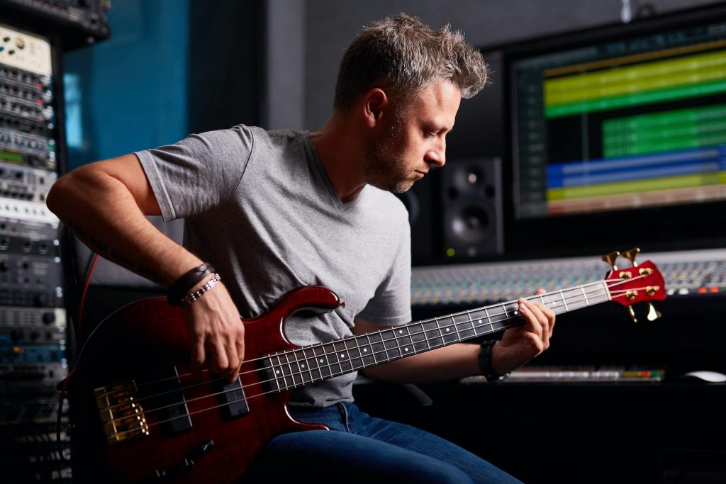 music producer playing guitar in recording studio