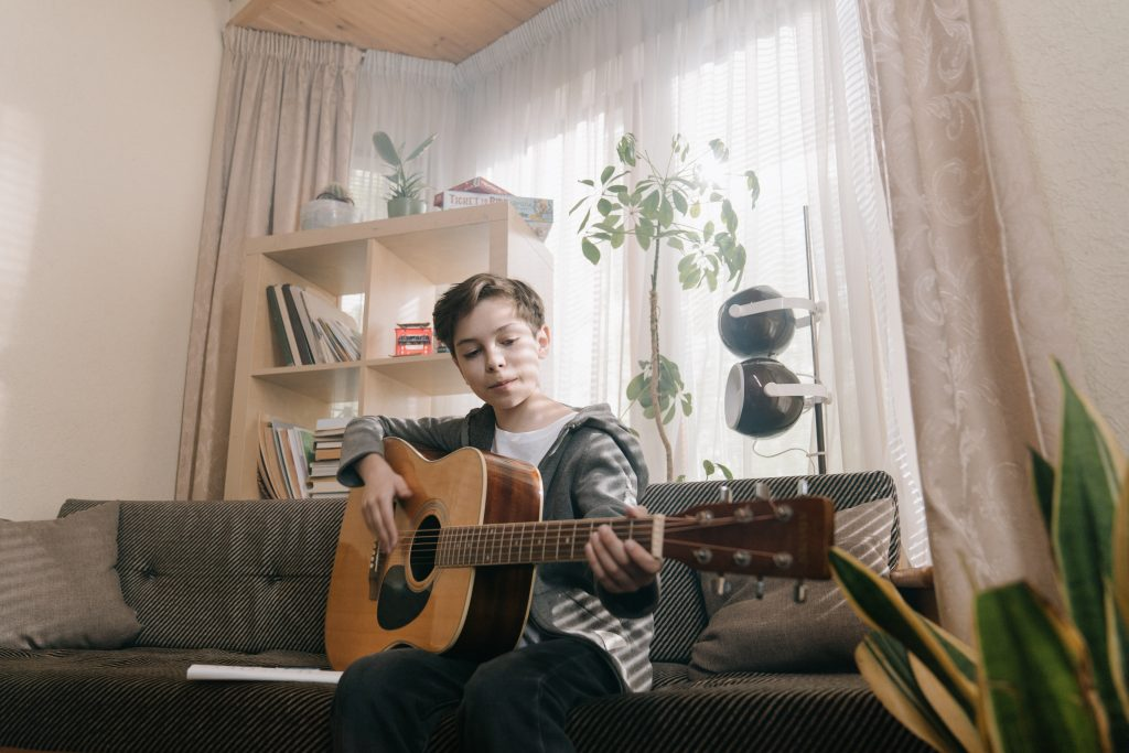 boy performing music guitar