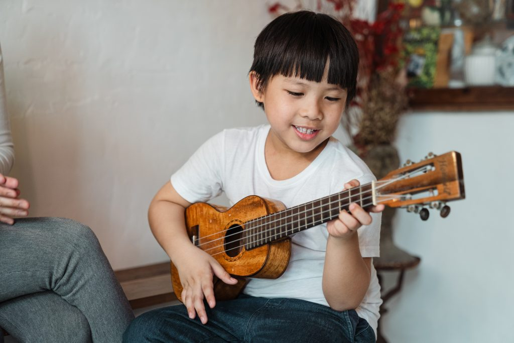 boy performing music ukulele