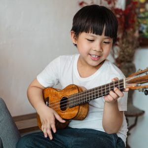 boy performing music ukulele