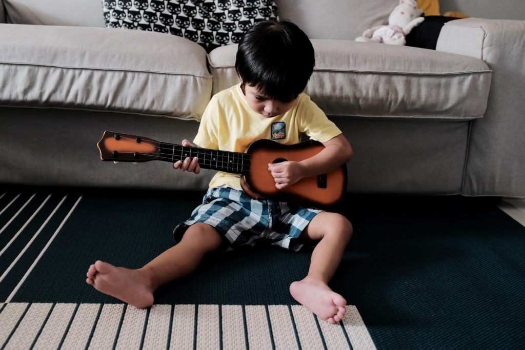 little boy playing the ukulele at home