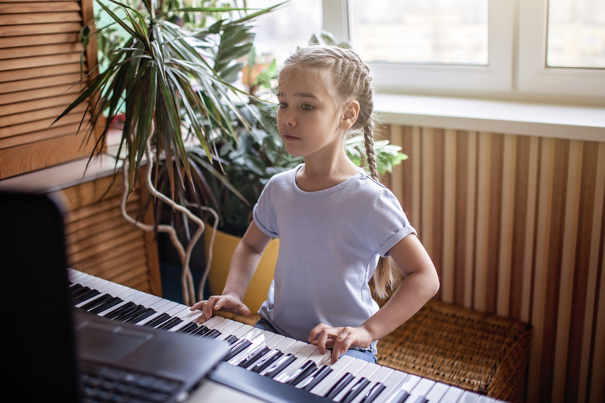 Young musician playing classic digital piano at home during online class at home, self-isolation