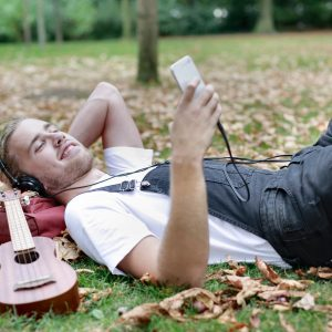 man listening to relaxing music while lying down in a park