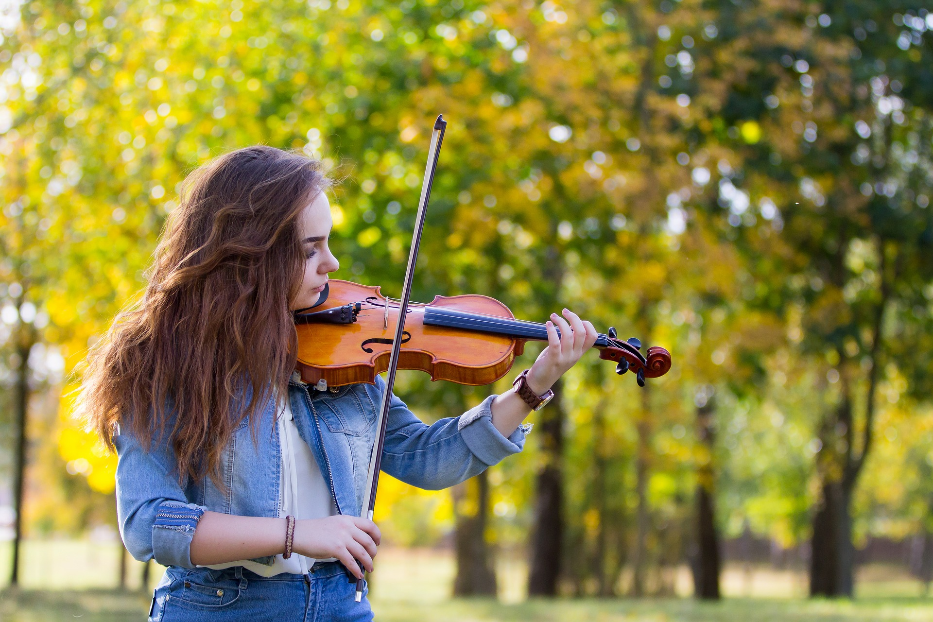 violinist playing the violin outdoors in a park