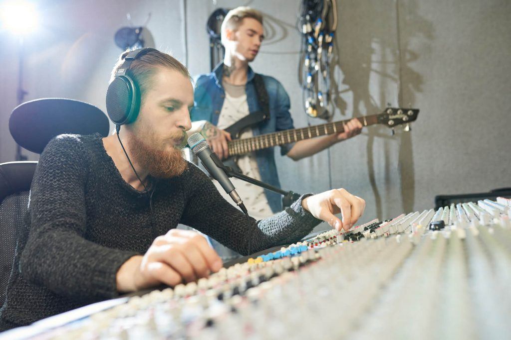 sound engineer and guitar playing in recording studio