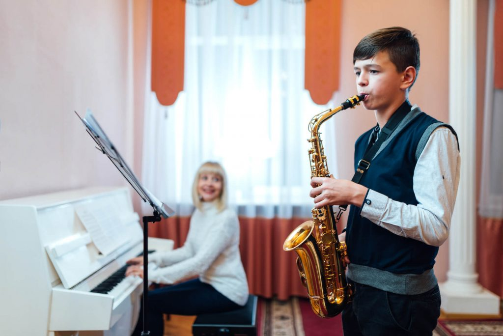 boy learning how to play saxophone with teacher