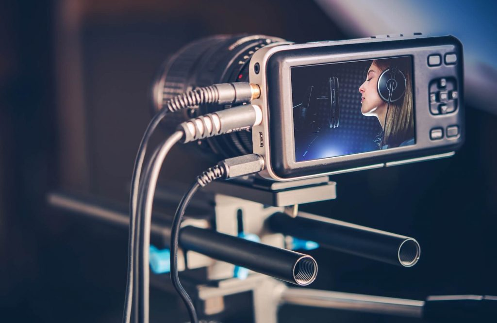 camera recording a singer in a studio