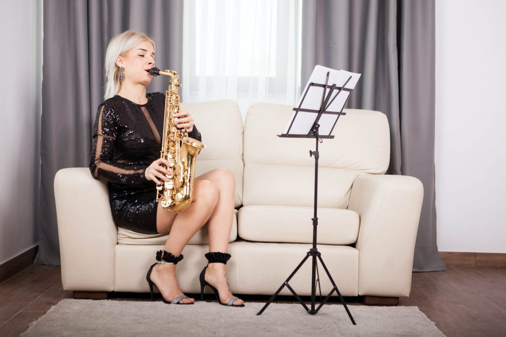 female playing saxophone in living room