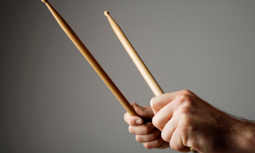 a man holding drumsticks while learning how to play drums