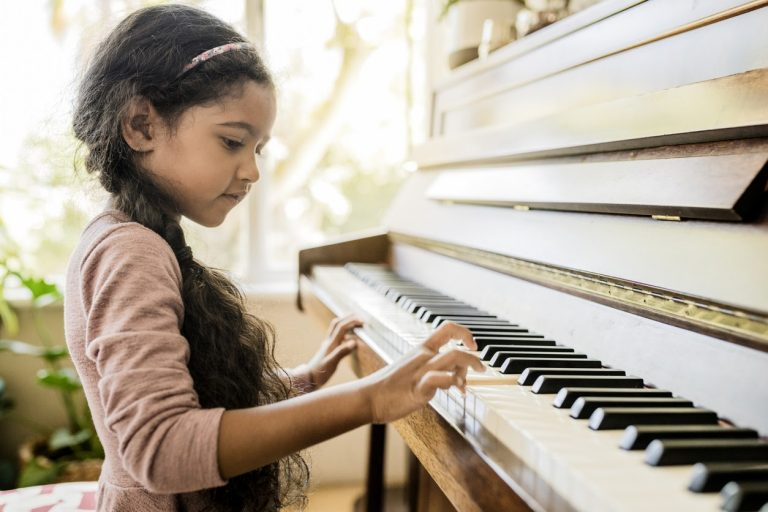 little girl learning piano for the first time