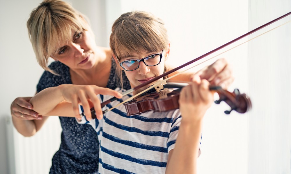 Teacher teaching student beginning violin
