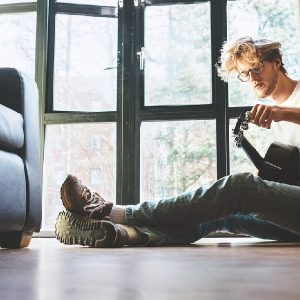 A musician sits on the floor and shows how to tune a guitar.