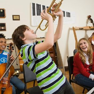 Five students have fun playing beginner instruments in a band.