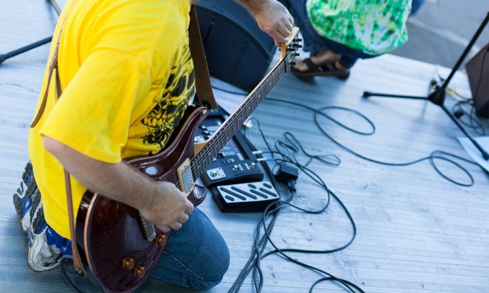 man tuning a guitar by ear