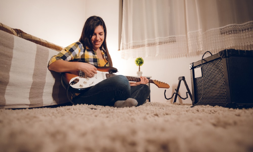 A female guitarist plays a guitar plugged into a combo guitar amp.