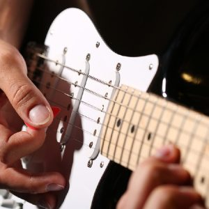 Man playing music after buying an electric guitar.