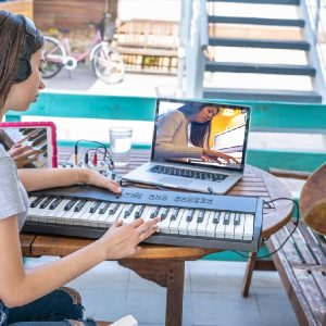 Young girl playing an electronic keyboard during online keyboard lessons