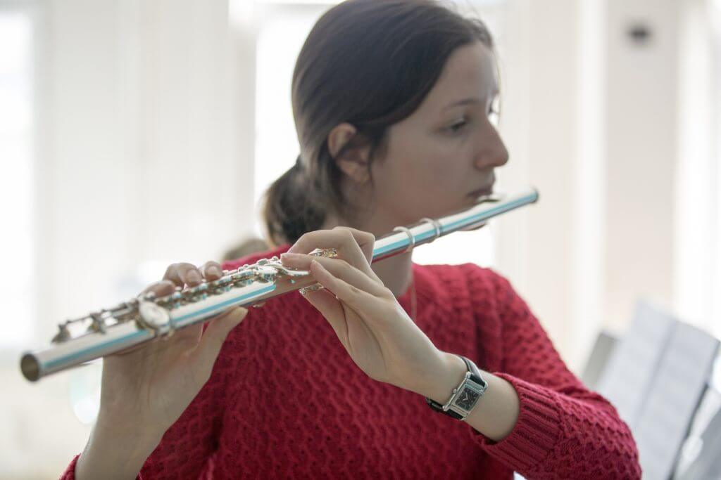 young female artist playing the flute