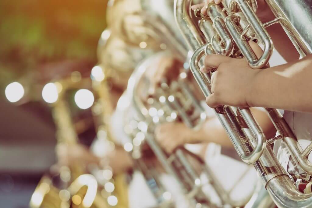 Male student with friends blow the euphonium with the band for performance on stage at night