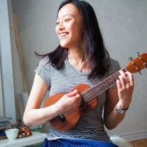 A young woman smiles while she plays her ukulele.